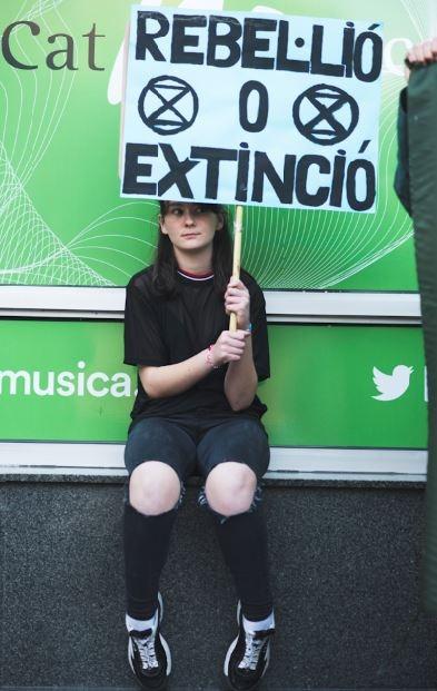 Noia amb una pancarta: Rebel·lió o Extinció