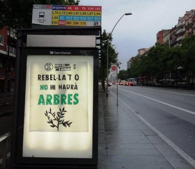 "Advertisment sign: ""Rebel or there will be no trees"" (in catalan) at a bus stop"