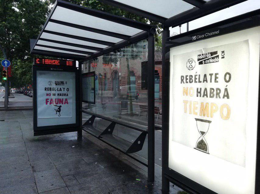"""Cartells: """"Rebel·la't o no hi haurà fauna"""", """"Rebelate o no habrà tiempo"""" a una parada d'autobús"""