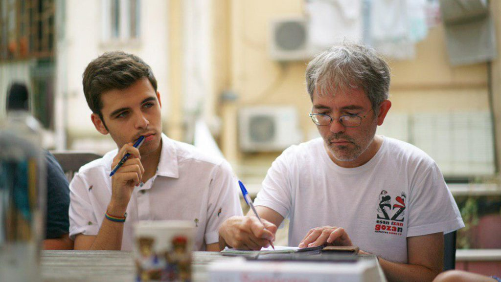 Two men with white t-shirts and pens in their right hand. One of them is thinking and the other is writing.