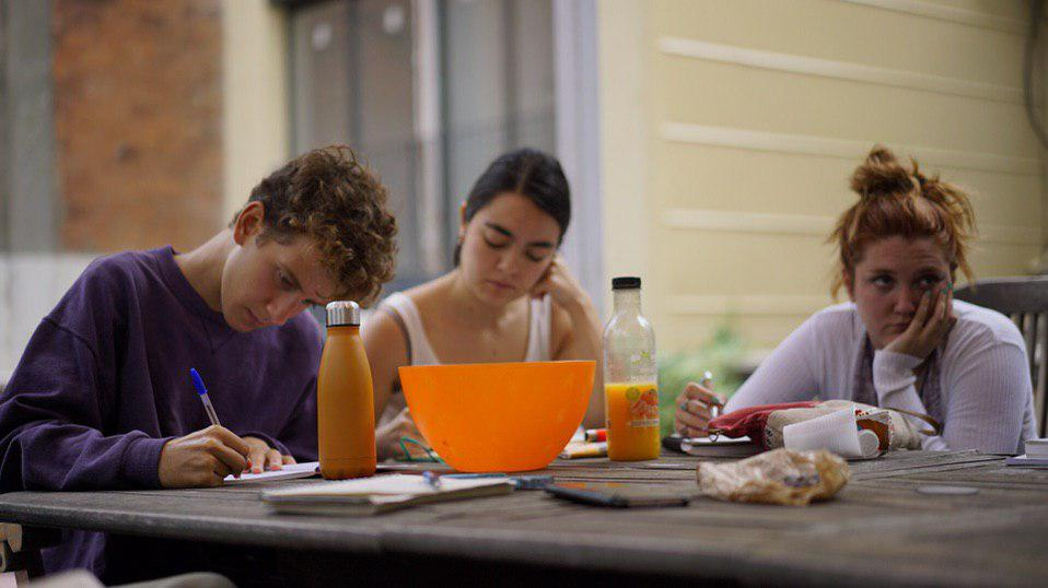 Three focused young people sitting around a table with food and writing supplies.