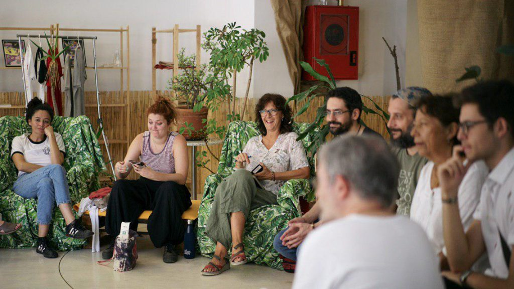A group of people sitting in a circle in a room with plants. They are having fun.