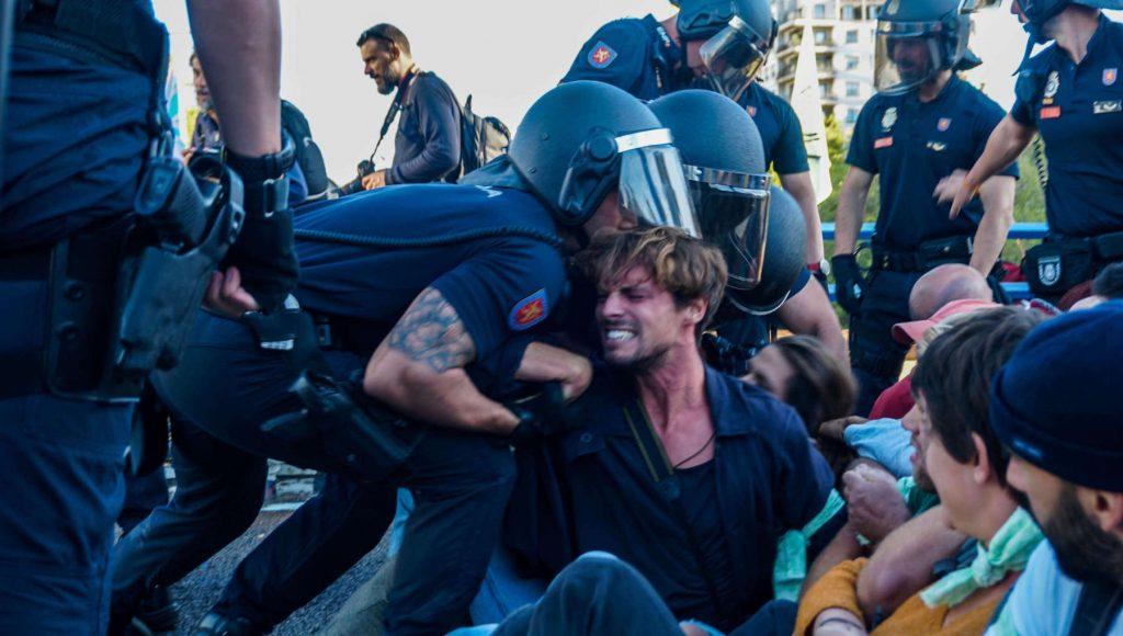 Imagen de un rebelde que se resiste pacíficamente contra la acción violenta de un policía.