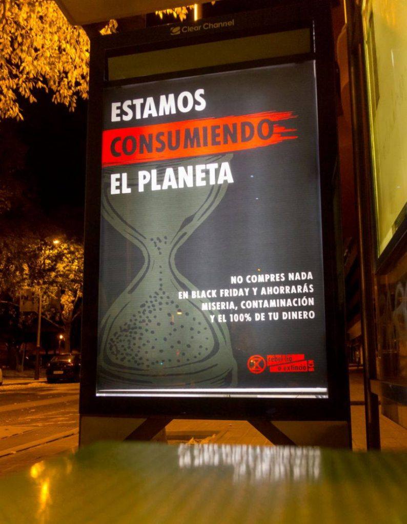 """Cartel: """"estamos consumiendo el planeta"""" en una parada de autobús"""