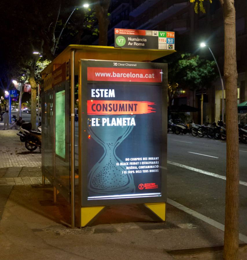 "Advertisment sign: ""we are consuming the planet"" (in catalan) at a bus stop"