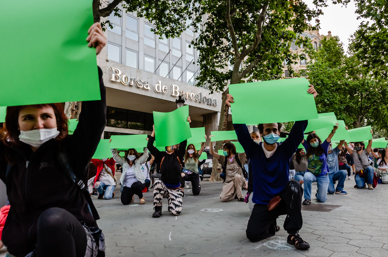 Rebels holding green posters in front of La Borsa de Barcelona
