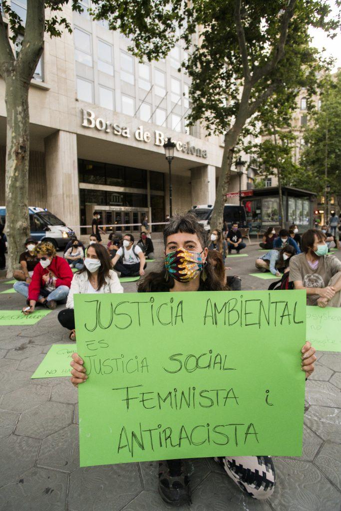"""Rebel amb cartolina verda i text """"Justícia ambiental és justícia social, feminista  i antiracista""""."""