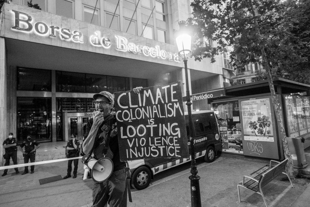 Rebelde con cartel ante La Bolsa de Barcelona el Día del Medio Ambiente